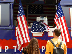 New York artist Maria Mihelic and Philadelphia artist David Gleesen drove a former Trump-Campaign bus turned art installation to the April 25, 2016 Trump rally. Inside the bus Mihelic  is seen working on art project as she embroiders American Flags with phrases Trump said during his campaign. Trump-Supporters and anti-Trump protestors face each other outside a rally of the Republican candidate, held at the campus of West Chester University in West Chester, Pennsylvania a day ahead of the Pennsylvania Primary.
