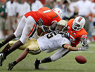 MIAMI, FL: Georgia Tech's Greg Smith (5) gets hit by   the University of Miami's Kenny Phillips and Bruce Johnson in the second half on Saturday,10/13/07 in Miami Florida. Tech won the game 17 to 14. ©2007 Johnny Crawford