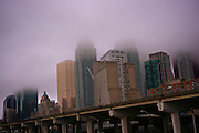 An eastern section of Toronto's skyline with the Gardiner Expressway in the foreground, on a foggy rainy evening.