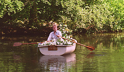 **This photograph was taken with the knowledge and approval of the Spencer family** The Spencer family's gamekeeper rows a boat carrying flowers left by mourners across to the island in the grounds of their home at Althorp, Northamptonshire where the body of Diana, Princess of Wales was laid to rest on Saturday.