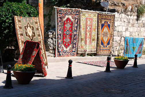 Turkish rugs displayed outdoors; pedestrian street; cobblestone; vendor; Antalya; Turkey