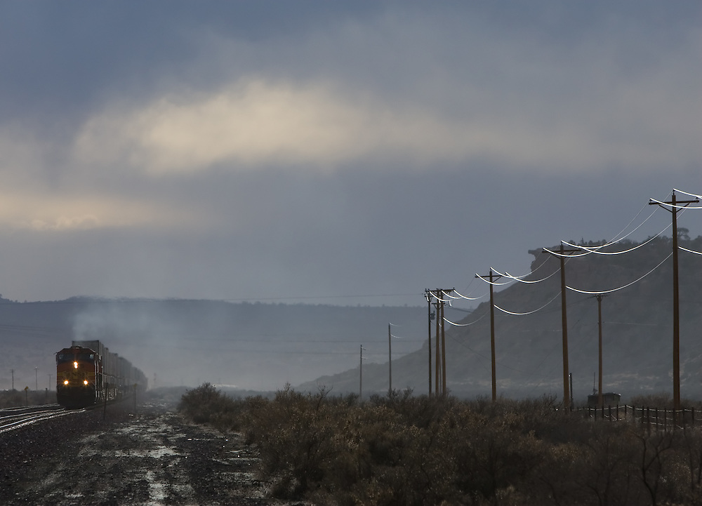A hint of sun is peaking through dark storm clouds as an eastbound intermodal train races toward Gallup, NM.
