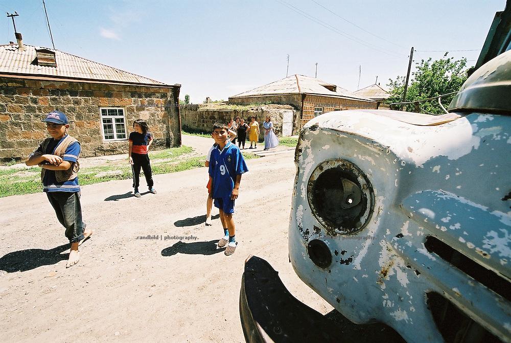 Eine Dorfszene in Armenien. Am Strassenrand steht ein stillgelegter Lastwagen russischer Bauart. Kinder spielen auf der Strasse, die in der Regel nicht asphaltiert sind. Boys on a street in the armenian village of Hoktember.
