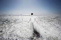 Man walking into sea being washed by waves back view