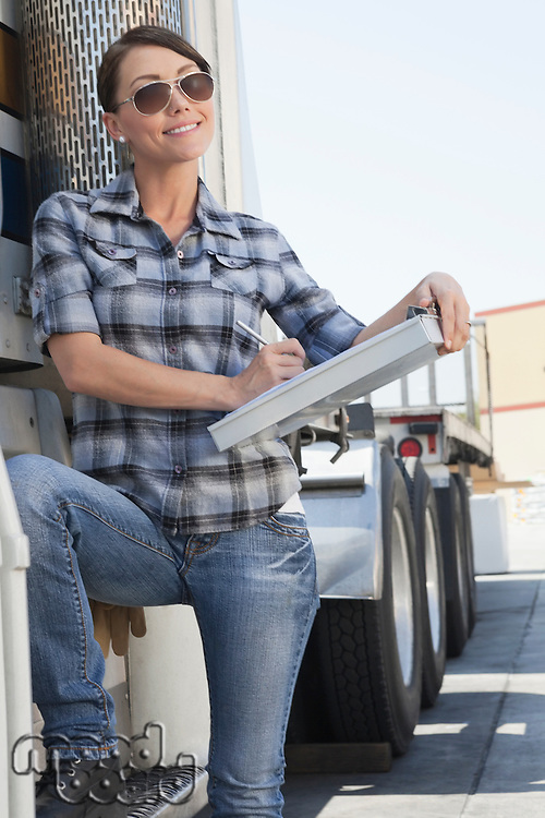 Beautiful woman writing on clipboard while standing by a flatbed truck