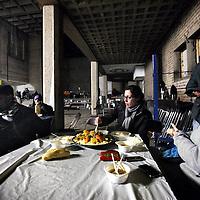 Nederland, Amsterdam , 4 december 2012..de gekraakte Sint Jozefkerk in Bos en Lommer..waar zo'n tachtig asielzoekers sinds zondag worden opgevangen. Ze bivakkeerden eerder in een tentenkamp in Osdorp..vooral jongeren springen voor deze vluchtelingen in de bres, maar ook allochtone buurtbewoners van zowel Marokkaanse als Turkse afkomst komen met pannen couscous  rijst en soep om de hongerige asielzoekers te voeden. Er is weinig electriciteit momenteel in de kerk en het is er koud..Op de foto: jonge vrijwilligers en asielzoekers tijdens het avondmaal..Foto:Jean-Pierre Jans