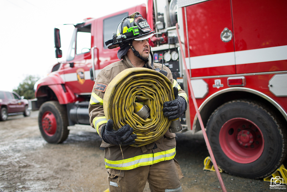 A Spring Valley Fire Department fire fighter carries a fire hose as multiple fire departments, including Milpitas Fire Department, Spring Valley Fire Department, and Cal Fire, work to contain and extinguish a structure fire at the 3000 block of Calaveras Road near Spring Valley Golf Course in Milpitas, California, on February 10, 2014. (Stan Olszewski/SOSKIphoto)