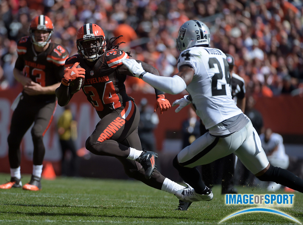 Sep 27, 2015; Cleveland, OH, USA; Cleveland Browns running back Isaiah Crowell (34) is defended by Oakland Raiders safety Charles Woodson (24) in the second quarter of a NFL game at FirstEnergy Stadium.