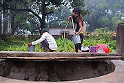 Next to her father, Babujan Mia, 48, Tabasum Khatun, 14, is collecting fresh water from a well near her home in Algunda village, pop. 1000, Giridih District, rural Jharkhand, India.