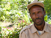 """Aliye Yesak, 40 at his home in Zwei, Ethiopia...Before Aliye and his wife, Momima, became involved in SEDA, an organisation working with Send a Cow, they used to live in a  grass house which leaked when it rained. During the drought he was forced to work on another farm as a labourer. He was paid 1 Birr a day, enough to buy one loaf of bread. As a result the family ate once a day and life was very tough. Sometimes he wasnt sure if his children would make it...""""8 years ago we had to survive from government food aid. There are reports now of drought in Ethiopia, but we have our own vegetables we have grown and we have seedlings we can sell"""""""