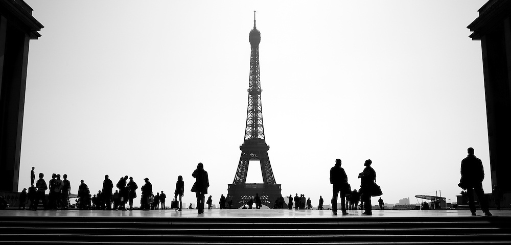 Tourists and vendors are silhouetted against a view of the Eiffel Tower from the Esplanade du Trocadero in Paris, France