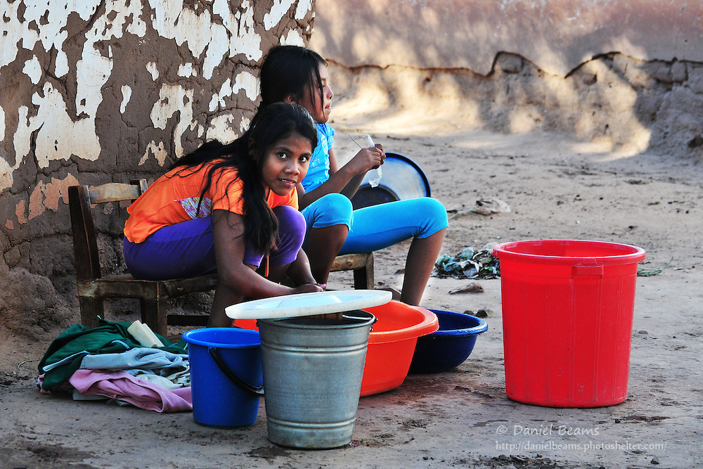 Guarani girls washing clothes by hand in Yapiroa, Charagua, Santa Cruz, Bolivia