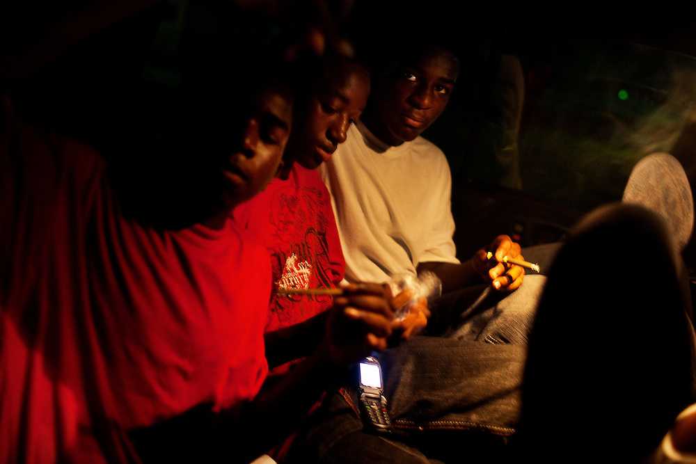 Young men in the Baptist Town neighborhood of Greenwood, Mississippi smoke marijuana in a car on Saturday, July 3, 2010.