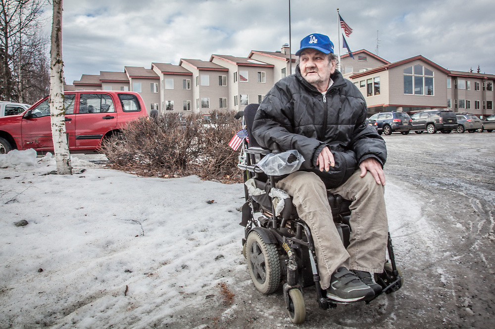"Disabled Korean War Veterane Dewey Kent takes a smoke break outside Providence Horizon House in east Anchorage.  ""I came to Alaska in 1984, got a divorce in 1989, and have not had a permanent place to live since.  I think I'm the only one in the whole place who smokes."""