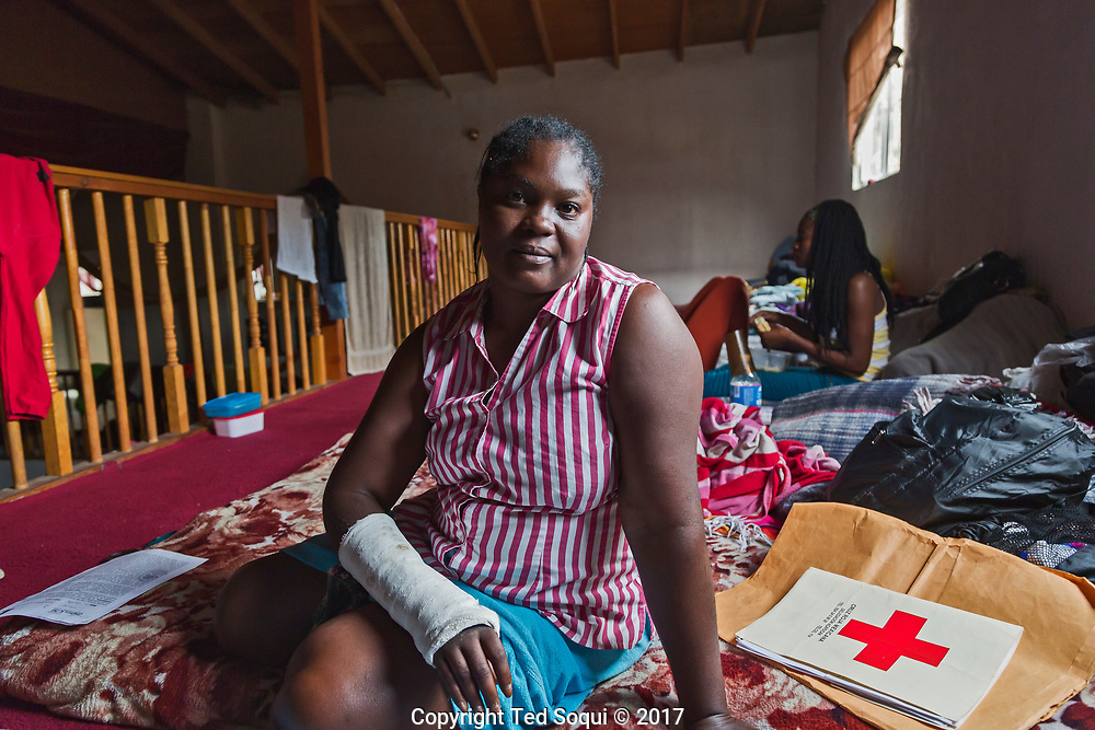 A young Haitian woman inside the church. She nearly died in a car accident on her long trip to Tijuana.<br /> The new community dubbed &quot;Little Haiti&quot; on Canon del Alacran (Scorpion Canyon). A church in the middle of the canyon has been turned in to a dormitory for the Haitian and African refugees. Some have started to build housing in the canyon, which may have been a tire dump previously. The stream running down the middle of the canyon reeks of pollution.<br /> Haitian immigrants.<br /> Tijuana, Mexico.