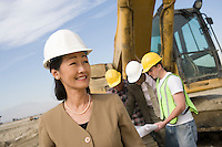 Female surveyor and construction workers on site