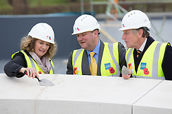 © Licensed to London News Pictures. 15/3/2016. Alrewas, Staffordshire, UK. National Memorial Arboretum Topping Out.<br /> Photo credit : Dave Warren/LNP.<br /> <br /> Pictured from left to right, SARAH MONTGOMERY (MD of the Arboretum), Lt Col DAVID WHIMPENNY (Chairman NMA Board), Major General PATRICK CORDINGLEY (Chair of the NMA Appeal Council).<br /> <br /> The highest stone that will clad the roof of the new, £15.7m Remembrance Centre at the National Memorial Arboretum (NMA) in Staffordshire was put in place earlier today.<br /> The ceremony will mark the half way point in the creation of the centre, which will educate, inform and inspire up to 500,000 visitors per year, and is on schedule for completion by the autumn.<br /> The facilities are being provided thanks to a major fundraising campaign, launched by HRH The Duke of Cambridge, along with generous donations from both Staffordshire County Council and the Heritage Lottery Fund.<br /> £11m has been raised so far and organisers continue to appeal for help in raising the remaining £4.7m required for the project. The Arboretum will remain open throughout the construction period.
