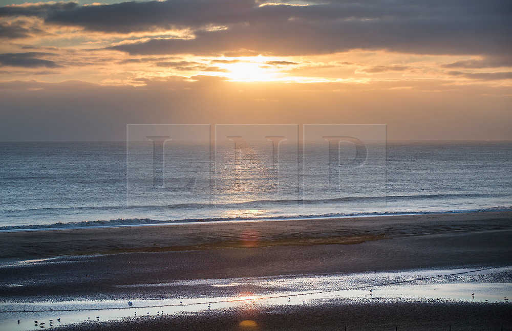 © Licensed to London News Pictures. 14/01/2017. Great Yarmouth, UK. First light on a calm day in Gorleston-on-Sea near Great Yarmouth. Hundreds of people are returning to their homes after flood warnings. A change in the wind direction stopped any major flooding to properties on the east coast of England.  Photo credit: Peter Macdiarmid/LNP