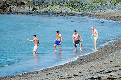 © London News Pictures. 05/05/2016. Aberystwyth, UK. Four young men enjoying a dip in the sea in  the warm spring sunshine in Aberystwyth Wales.  The temperature is forecast to rise over the coming days,  as a plume of warm air moves in from the near continent,  reaching the low 20's centigrade by the weekend. Photo credit: Keith Morris/LNP