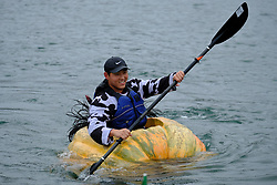 A man races a giant pumpkin across Lake of the Commons at the 14th annual West Coast Giant Pumpkin Regatta in Tualatin, Ore. on October 21, 2017. (Photo by Alex Milan Tracy)
