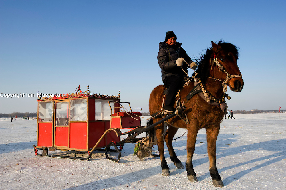 Horse drawn carriage on frozen Songhua RIver during ice festival in Harbin China 2009