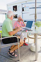 A mature couple using laptop computers outside their trailer on their patio while one talks on the phone...Model Releases.20070822_MR_C.20070822_MR_D.20070822_PR_A
