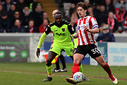 Lincoln City midfielder Alex Woodyard (30) watched by Exeter City midfielder Hiram Boateng (44) during the EFL Sky Bet League 2 match between Lincoln City and Exeter City at Sincil Bank, Lincoln, United Kingdom on 30 March 2018. Picture by Mick Atkins.