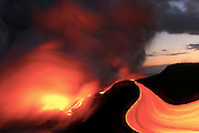 Fiery lava streams towards the Pacific Ocean exiting a lava tube at the base of the Kilauea Volcano on the Big Island of Hawaii. Erupting for over two decades now the island continues to grow while putting on dramatic and visually impressive shows.