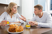 Mid adult couple talking while having breakfast at home
