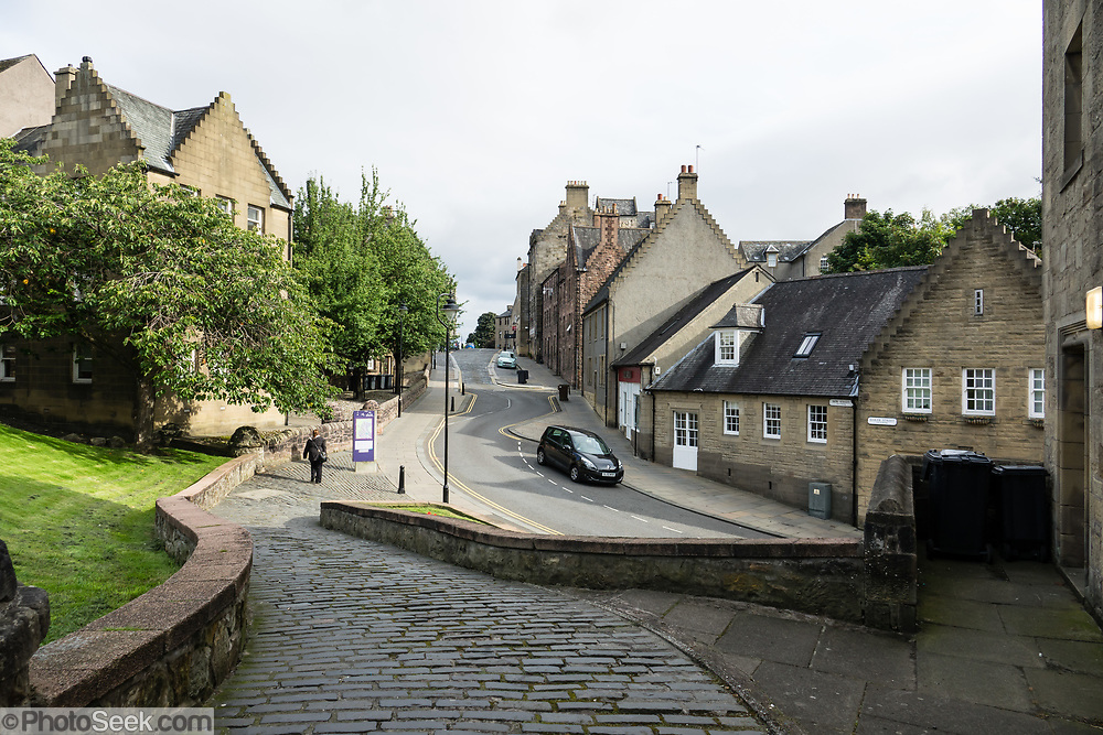 Medieval street in Stirling, Scotland, United Kingdom, Europe. Once the capital of Scotland, Stirling is visually dominated by Stirling Castle, in the United Kingdom, Europe. Historically, Stirling controlled a strategic position (until the 1890s) as the lowest bridging point of the River Forth before it broadens towards the Firth of Forth, making it the gateway to the Scottish Highlands. One of the principal royal strongholds of the Kingdom of Scotland, Stirling was created a royal burgh by King David I in 1130. Stirling Castle sits atop Castle Hill, an intrusive crag, which forms part of the Stirling Sill geological formation. Most of the stronghold's main buildings date from the 1400s and 1500s, when it peaked in importance. The outer defences fronting the town date from the early 1700s. Before the union with England, Stirling Castle was also one of the most used of the many Scottish royal residences, serving as both a palace and a fortress. Several Scottish Kings and Queens have been crowned at Stirling, including Mary, Queen of Scots in 1542, and others were born or died there. Stirling Castle has suffered at least eight sieges, including several during the Wars of Scottish Independence, with the last being in 1746, when Bonnie Prince Charlie unsuccessfully tried to take the castle.