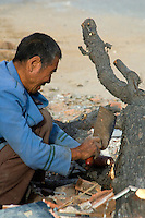 "China, Beijing, Chaoyang, San Jian Fang, 2008. Virtually everything made of wood is this recycler's goal, using little more than a traditional Chinese kitchen knife and a ""sanluche,"" or three-wheel bicycle cart."