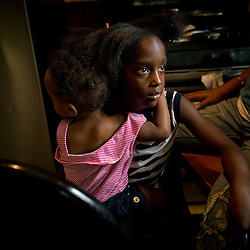Siobhan Washington' granddaughters  Marianna Hildreth, 7, holds her cousin Mariyah McGhee's, 1, who suffers from  Asthma in her home in River Rouge, Detroit, near a DTE coal plant August 13, 2012.