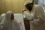 Sheikh Reda Shata, an Egyptian born Imam visiting a mother and her new born baby in a Brooklyn hospital.  He holds the newborn as he says a blessing.