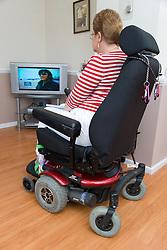 Older woman wheelchair user watching TV,