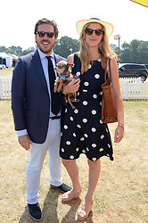 WILLIAM WOODHAMS and ANNABEL SIMPSON holding her dog Coco at the Veuve Clicquot Gold Cup, Cowdray Park, Midhurst, West Sussex on 21st July 2013.