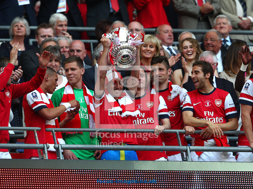 Santi Cazorla ( C ) of Arsenal lifts the trophy after his team win the The FA Cup Final match at Wembley Stadium, London<br /> Picture by Paul Terry/Focus Images Ltd +44 7545 642257<br /> 17/05/2014