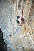 """Belayed by Alex Honnold, Tommy Caldwell climbs the third pitch (13a/b) of Todd Skinner's route """"Wet Lycra Nightmare,"""" on Leaning Tower, Yosemite National Park."""