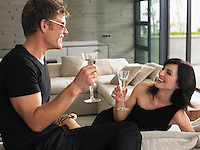 Couple sitting with champagne in living room