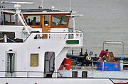Nederland, Waal, 7-5-2013Druk verkeer van binnenvaartschepen op de waal, rijn, vooral op en neer het duitse ruhrgebied en de haven van rotterdam. Een matroos, dekkracht, pleegt onderhoud terwijl de schipper in zijn stuurhut aan het roer zit.Foto: Flip Franssen/Hollandse Hoogte
