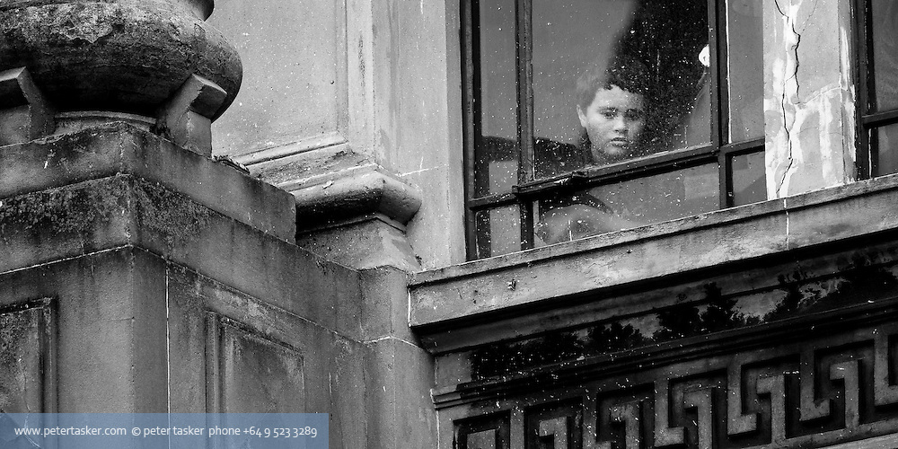 A boy looking out the window of an ornate commercial building during the 2011 Rugby World Cup. Queen Street, Auckland, New Zealand.