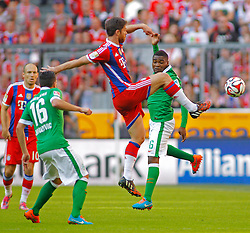 MUNICH, GERMANY - OCTOBER 18: Xabi Alonso of Bayern Munichand Cedric Makiadi of Werder Bremen compete for the ball during the Bundesliga match between Bayern Munich and Werder Bremen. October 18, 2014 in Munich, Germany. Photo mandatory by-line: Mitchell Gunn