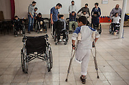 Malik Khaled stands infront of a group of Syrians injured by the ongoing conflict participate in a lesson on how to move and use wheelchairs. Reyhanli, Turkey 01/12/2013 Bradley Secker for the Washington Post