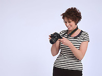 Mid adult woman holding digital camera studio shot