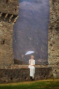 a woman in a white period dress is sitting on a stone wall with a parasol