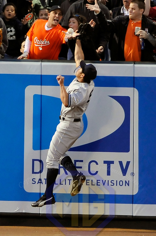 06 April 2009:  New York Yankees left fielder Johnny Damon (18) leaps in an attempt to catch a 2-run home run off the bat of Baltimore Orioles shortstop Cesar Izturis in the 8th inning as fans in the stand reach to catch the ball at Camden Yards in Baltimore, MD.  The Orioles defeated the Yankees 10-5 in the home opener to start the major league regular season.  (Mandatory Photo Credit: Mark Goldman - ICON/SMI)  ****For Editorial Use Only****