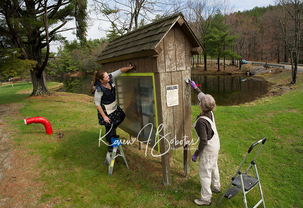 Jennifer Anderson and Carolyn Rudy sand a kiosk prior to a fresh coat of paint at Gunstock's pond during Laconia Rotary's volunteer service project on Saturday morning.  (Karen Bobotas/for the Laconia Daily Sun)