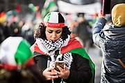 Frankfurt am Main | 16.12.2017<br /> <br /> On Saturday, December 16, 2017 about 1000 men, women and children take part in a demonstration march against the declaration of U.S. president Donald Trump to recognize Jerusalem as the capital of Israel and to relocate the U.S. Embassy in Israel from Tel Aviv to Jerusalem. The demonstration was registered under the slogan &quot;Demo f&uuml;r Jerusalem - Jerusalem/Alkudus ist die Hauptstadt Pal&auml;stinas&quot; (Demo for Jerusalem - Alkudus is the capital of Palestine).<br /> Here: A female protester (woman) with a kufiya ad a cap in the colors of the flag of Palestine ist looking at her smartphone.<br /> <br /> photo &copy; peter-juelich.com<br /> <br /> - Foto honorarpflichtig<br /> - No Model Release<br /> - No Property Release