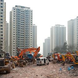 Chongqing - 1 febbraio 2011: gru ed escavatori parcheggiati in una zona residenziale in costruzione di RenHe, a nord della città. Chongqing - February 1, 2011: excavators and bulldozers in an under-construction residential area in Renhe, in northern Chongqing.