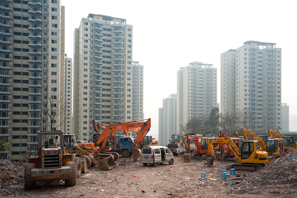 Chongqing - 1 febbraio 2011: gru ed escavatori parcheggiati in una zona residenziale in costruzione di RenHe, a nord della città. Chongqing - February 1, 2011: excavators and bulldozers in an under-construction residential area in Renhe, in northern Chongqing. Chongqing, China - The most populous city in the world