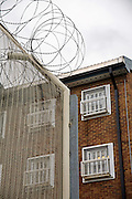 Security fencing around HMP Coldingley. HMP Coldingley, Surrey was built in 1969 and is a Category C training prison. Coldingley is focused on the resettlement of prisoners and all prisoners must work a full working week within the prison. Its capacity is 390 prisoners.